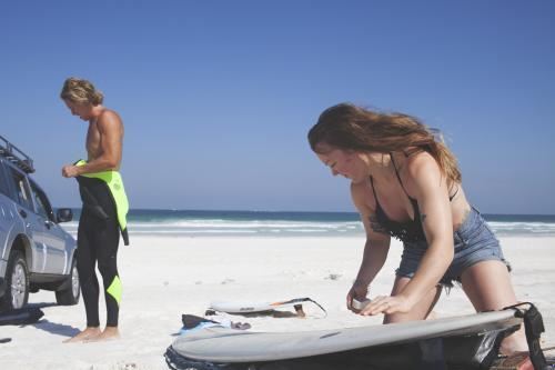 Male and Female friend prep for surf in Western Australia