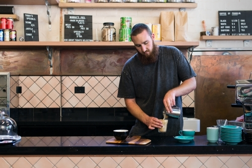Male barista making coffee inside cafe