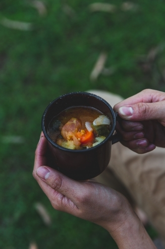 Male hands holding hot mug of soup, sitting on grass on cold afternoon