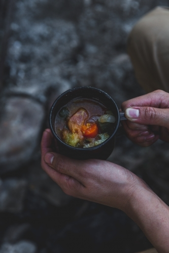 Male hands holding warming mug of soup, sitting beside old campfire on cold evening