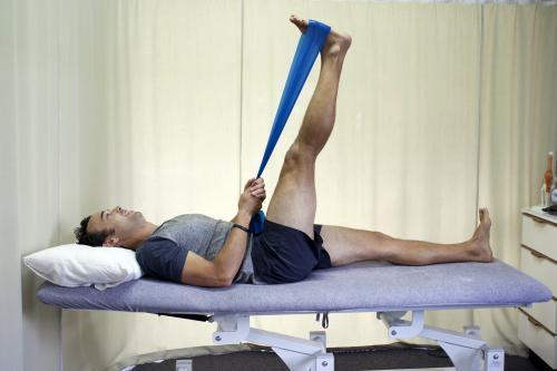 Male patient completing a hamstring stretch on a bed in a physio studio