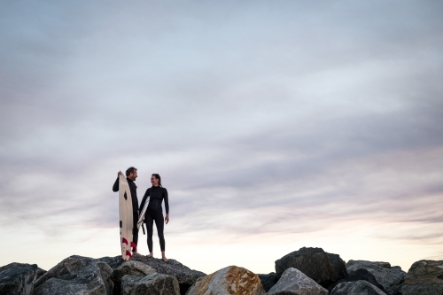 Man and Woman couple standing on coastal rocks holding surfboards looking at each other at sunset