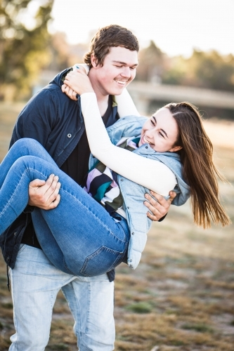 Man carrying girlfriend in arms laughing