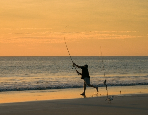 Man Casting a Surf Rod on Cable Beach at Dusk