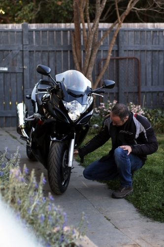 Man crouching next to motorbike in garden