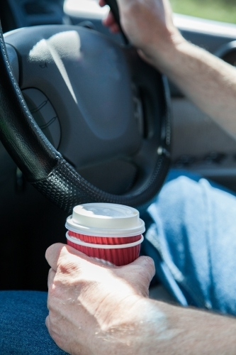 Man holding a coffee in a takeaway cup while driving