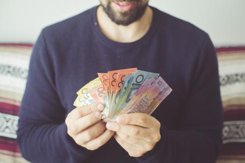 Man holding a selection Australian currency notes