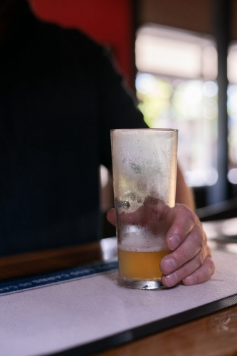 Man holding an almost empty glass of beer