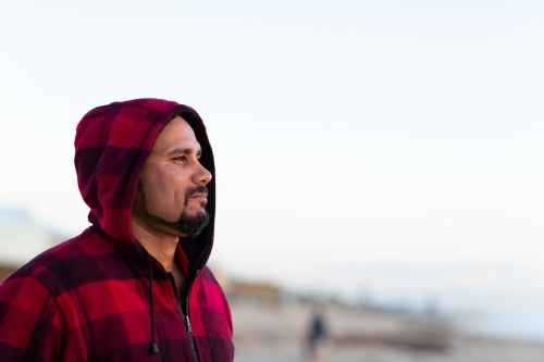 man in profile wearing red checked hoody