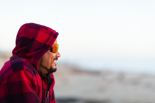Man in red checked hoody with face in profile wearing sunnies