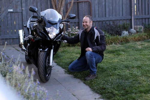 Man laughing and crouching next to motorbike in garden