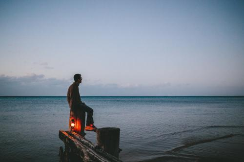 Man on old wooden jetty with lamp at dusk