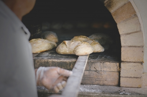 Man pulling out freshly baked bread from wood oven.