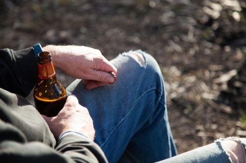 Man relaxing outside holding a bottle of beer