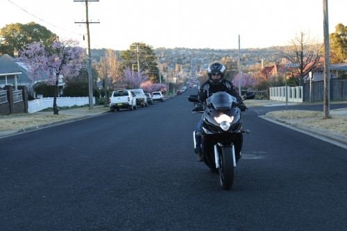 Man riding motorbike on a suburban street