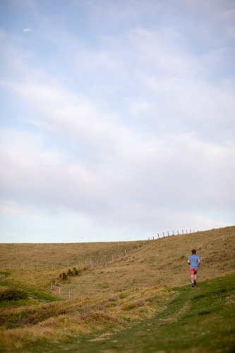 Man Running Uphill From Distance Under Blue Sky