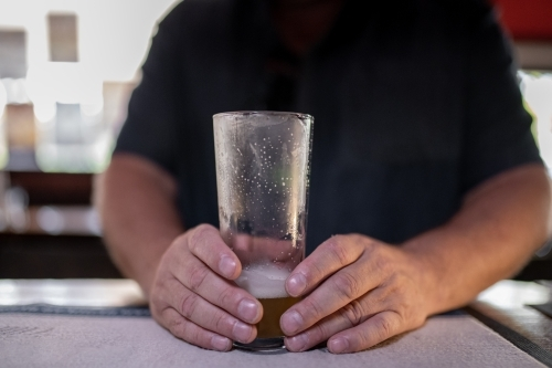 Man's hands holding almost finished glass of beer at a bar