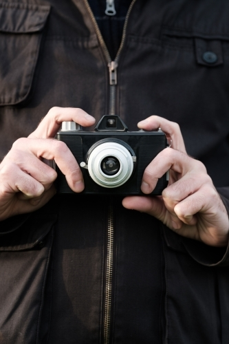 Man's hands holding vintage film camera