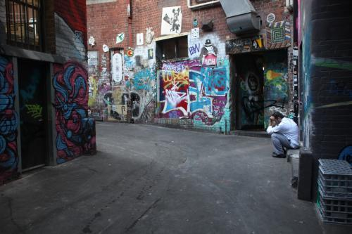 Man sitting in empty alley with graffiti on walls