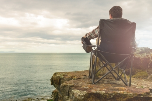 man sitting in tranquil camp spot by the ocean in his chair