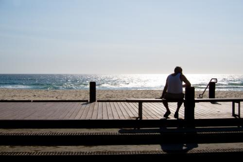 Man sitting on a bench silhouetted against the sun and sea