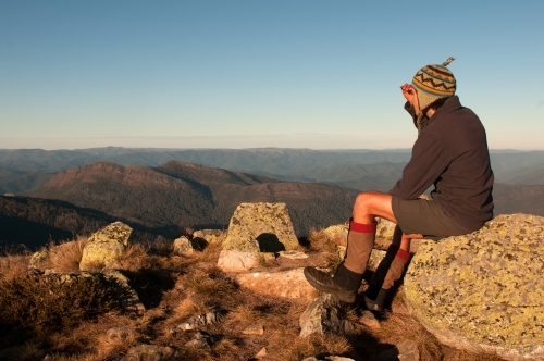 Man sitting on a rock looking out over mountain range