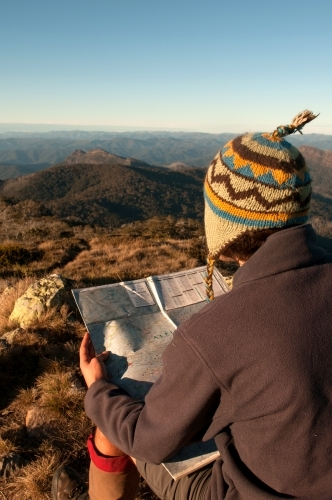 Man sitting on a rock overlooking mountain ranges, looking at a map.