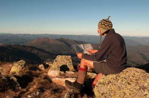 Man sitting on a rock overlooking mountain ranges, looking at a map