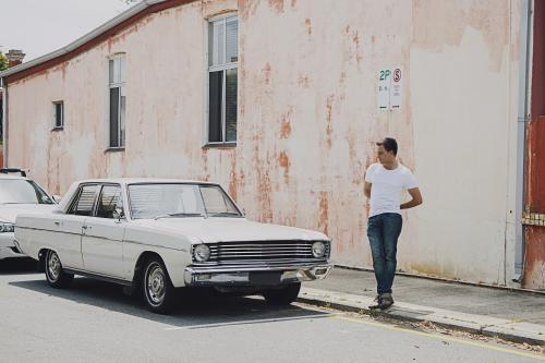 man standing in front of street sign admiring car