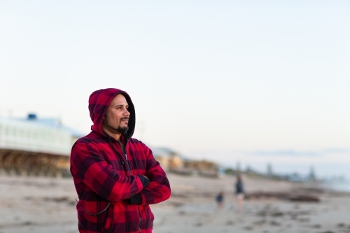 Man standing outdoors with arms crossed wearing red checked hoody