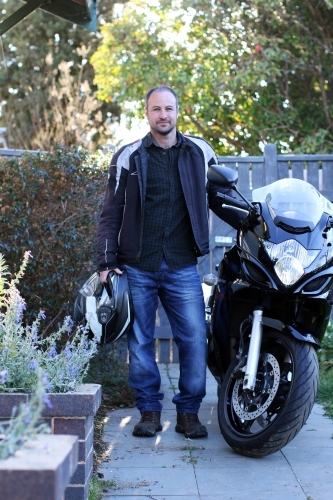 Man standing with motorbike in front of fence