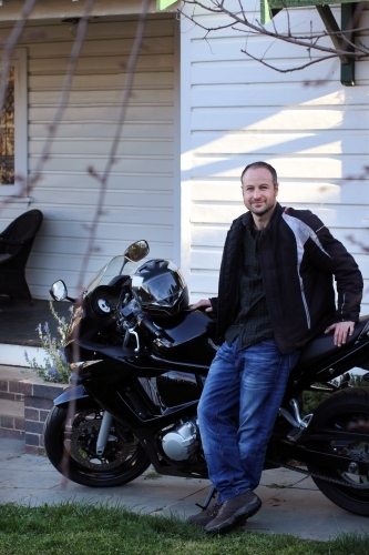Man standing with motorbike outside of house