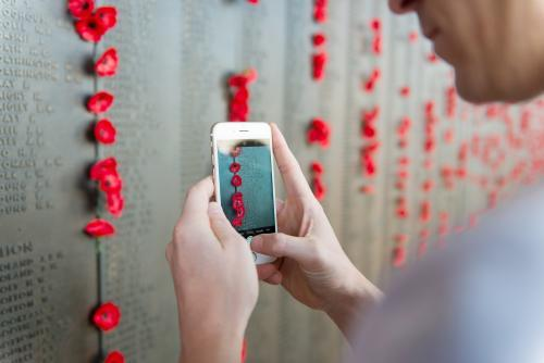 Man taking a photo with his mobile phone at the Australian War Memorial