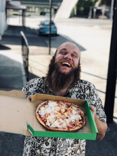 Man with a big smile holding up a pizza