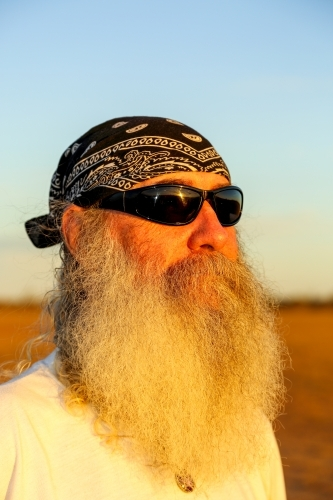 Man with full beard, sunglasses, and head scarf.