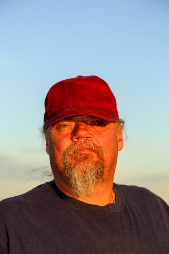 Man with a goatee beard in maroon cap, looking at camera..