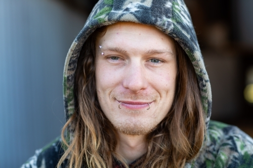 man with long hair in a hoodie face towards camera