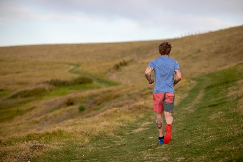 Man with Tattoo Running Alone in Countryside