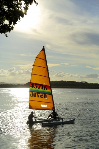 Two men launch catamaran on the Maroochy River.