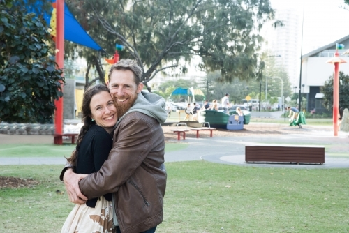 Married couple hugging tightly while smiling at the camera at the park.