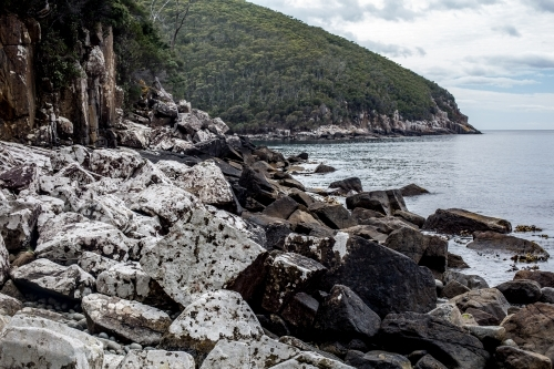 Massive boulders covered in white lichen line the coast  as Cape Hauy rises in the background