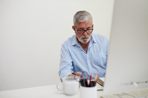 Mature business man sitting at a white desk, working on a computer