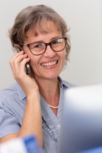 Mature business woman holding phone to ear