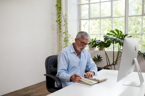 Mature businessman sitting at a desk, reading in an open-plan office