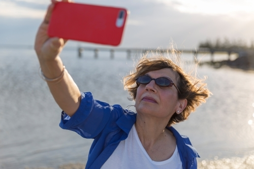 Mature middle eastern woman taking selfie on beach