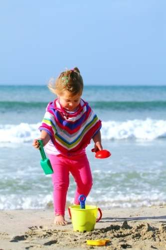 A two year old girl wearing a colourful poncho plays on a beach with her plastic toys during winter.