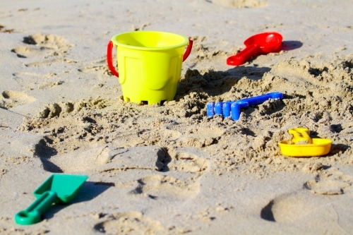 Colourful plastic bucket, rake, shovel and other toys on a sandy beach.