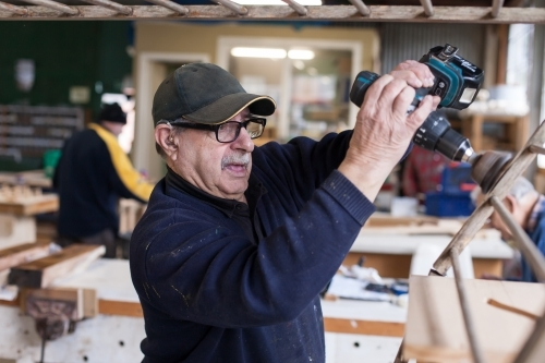 Man using a drill at a Men's shed