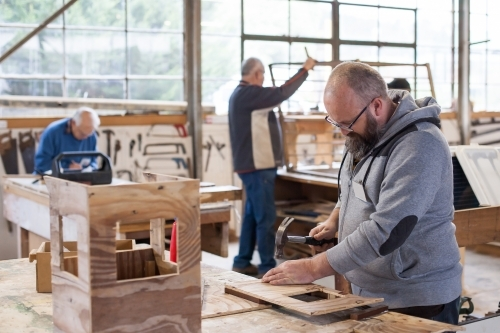 Man working at a Men's shed with men in background