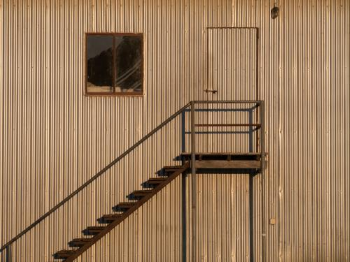 Metal steps on the side of a large corrugated building